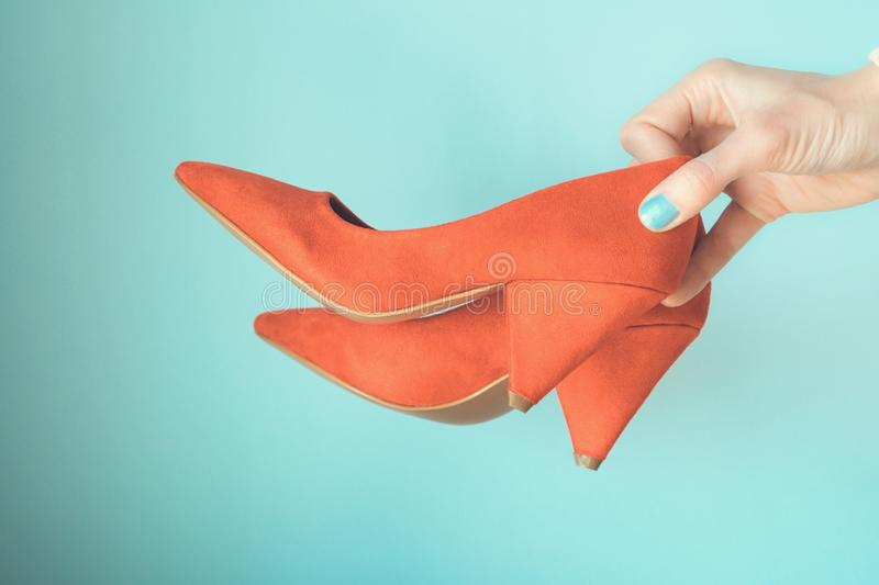 Woman holding red high heels in hand on blue stock photo