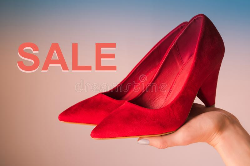 Woman holding red high heels on hand. Word Sale. Woman holding red high heels on hand on blue and pink background with word Sale. Shopping concept stock photo