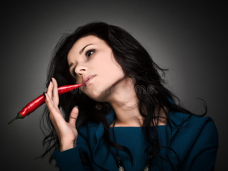 Woman Holding Red Hot Chili Pepper In Mouth Stock Image