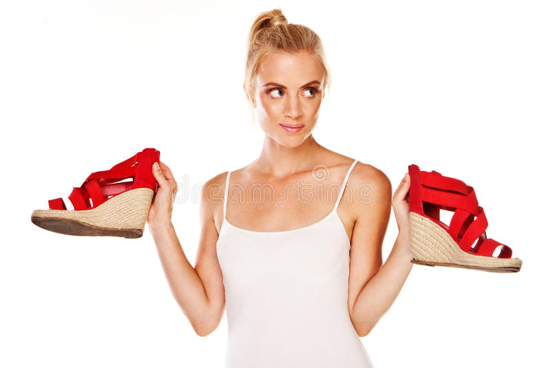 Woman holding red sandals. Attractive blonde woman holding up a pair of red sandals in her hands and looking up to heaven as though for inspiration royalty free stock photos