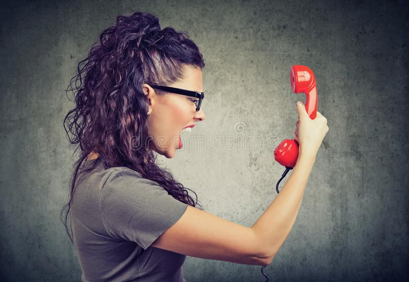 Woman holding red telephone receiver and yelling in anger. Side view of beautiful woman holding a red telephone receiver and yelling in anger stock images