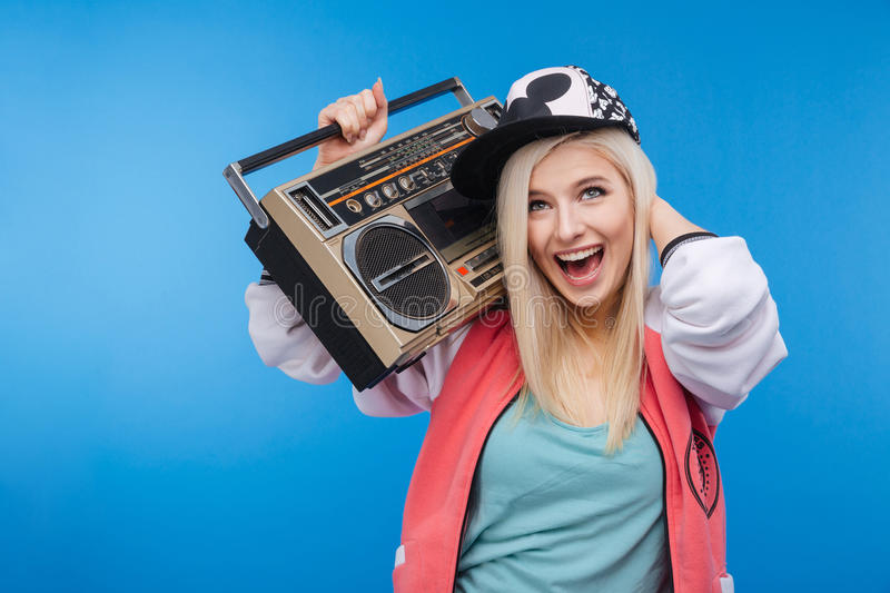 Woman holding retro boom box. Cheerful young woman holding retro boom box on blue background stock photography