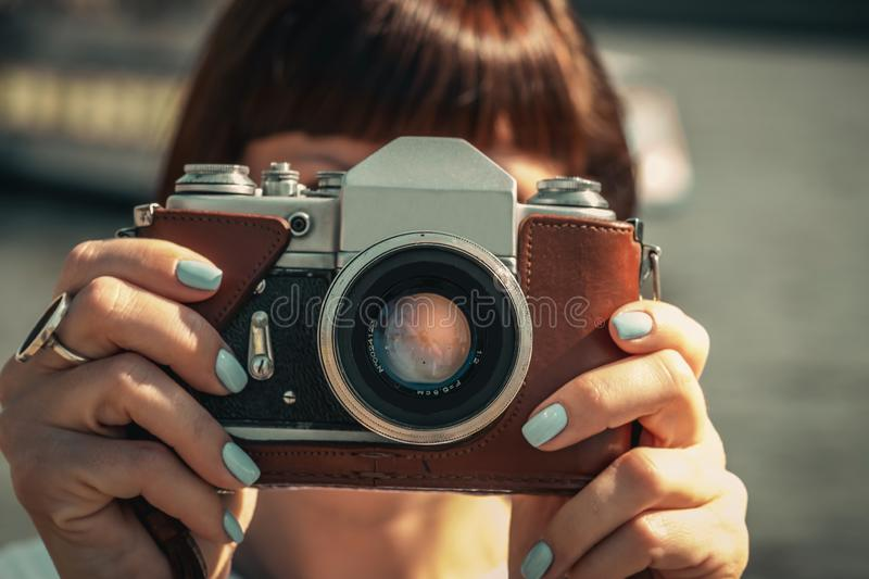 Woman holding retro vintage camera outdoors. Old camera. Female photography. royalty free stock photo