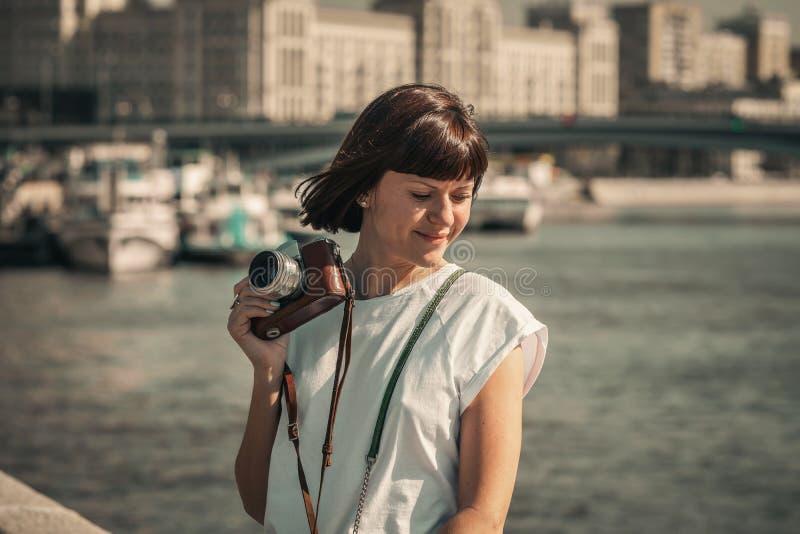 Woman holding retro vintage camera outdoors. Old camera. Female photography. stock image
