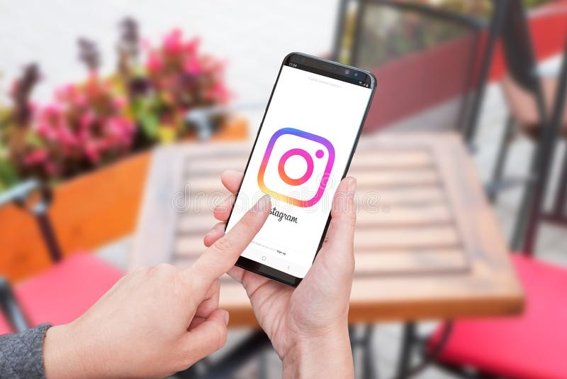 Woman holding Samsung Galaxy smart phone with Instagram stock photography