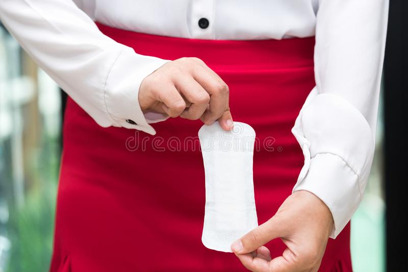 Woman holding sanitary napkins with red skirt - woman on her per. Iod royalty free stock photo