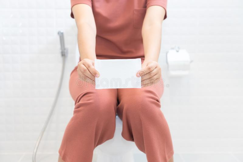 Woman holding sanitary napkins and sitting on toilet - woman on. Her period royalty free stock images