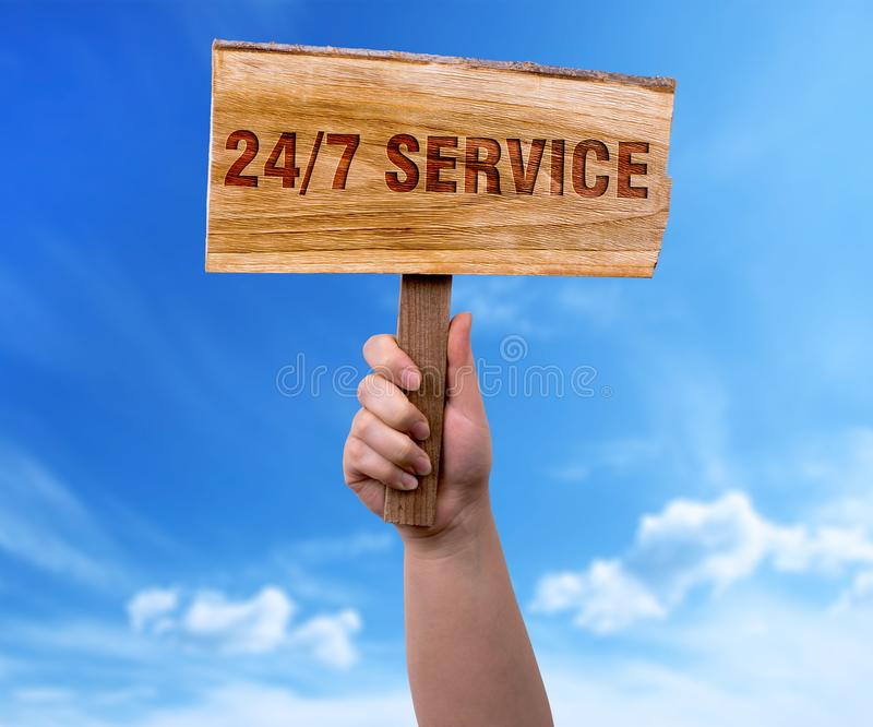 24/7 service. A woman holding 24/7 service wooden sign on blue sky background stock photo