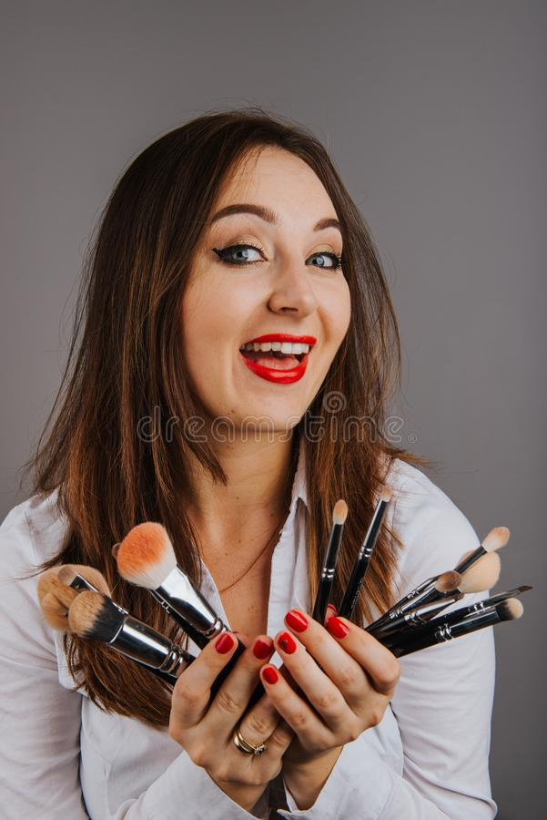 Woman holding a set of cosmetic brushes for make-up royalty free stock image