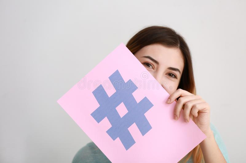 Woman holding sheet of paper with hashtag sign on light background royalty free stock image