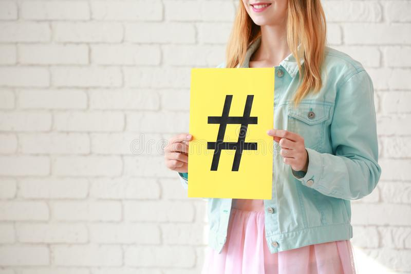 Woman holding sheet of paper with hashtag sign on white brick background royalty free stock photo