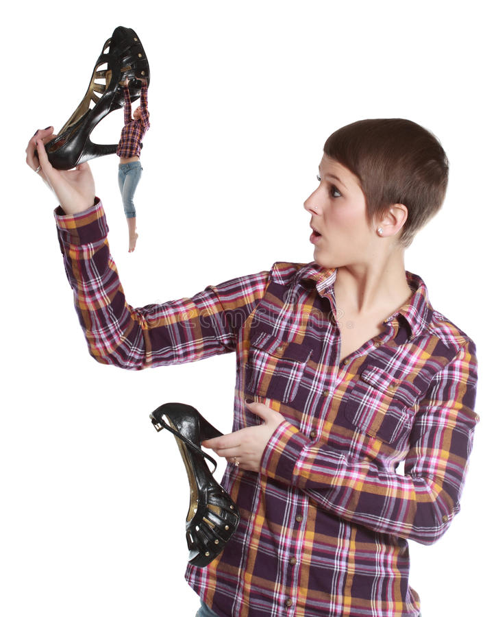 Woman holding a shoe climbed by a tiny girl stock photography