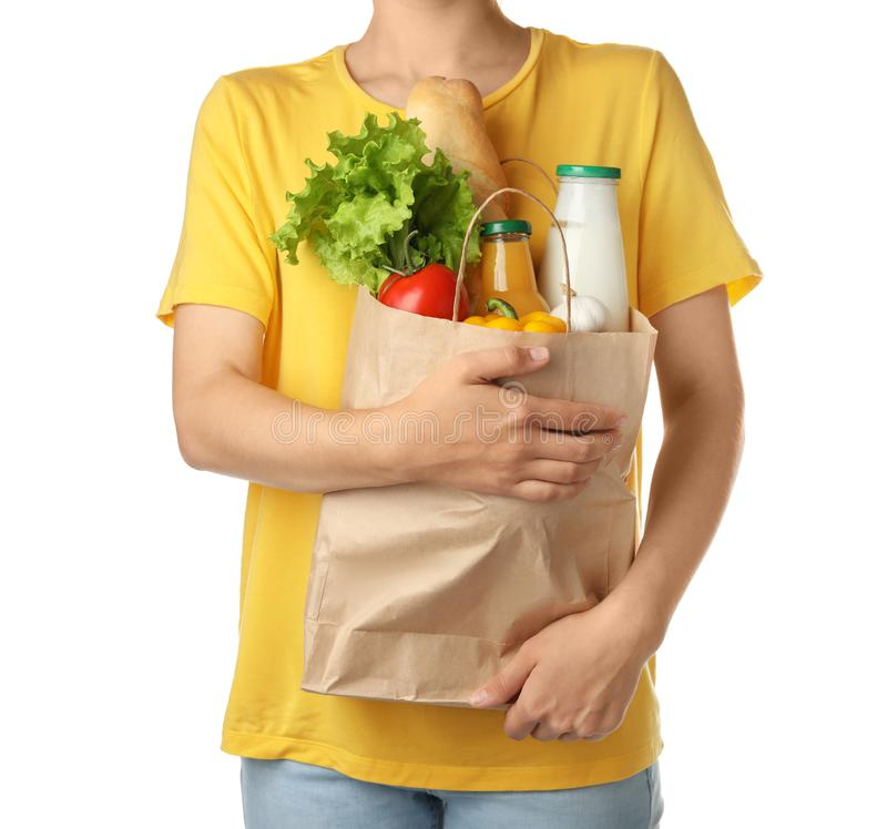 Woman holding shopping bag with different groceries on white background stock photography