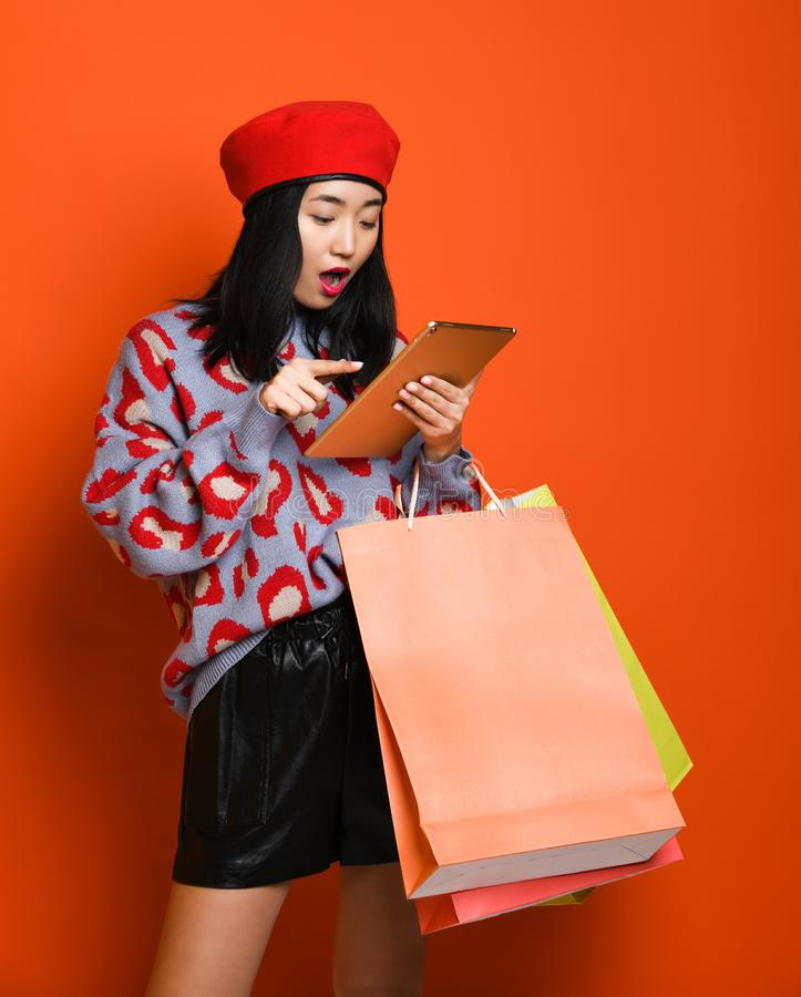 Woman holding shopping bag and using tablet for shopping online, shopping concept. Beautiful young happy Asian woman in a stylish beret and sweater, with a stock images