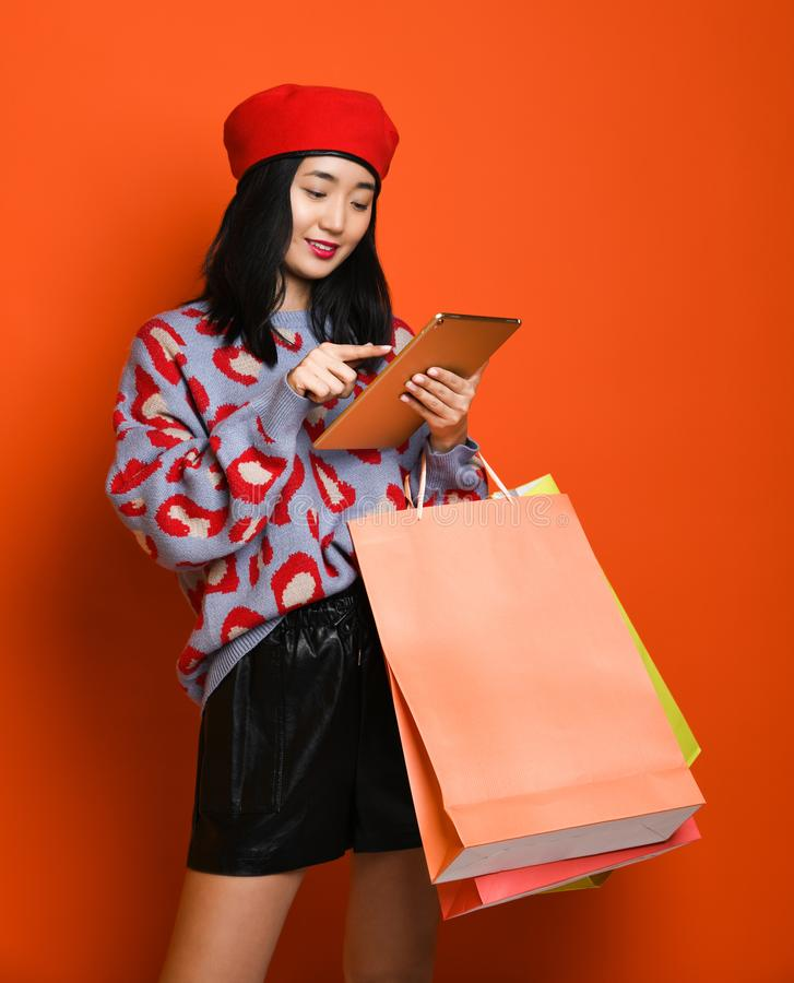 Woman holding shopping bag and using tablet for shopping online, shopping concept. Beautiful young happy Asian woman in a stylish beret and sweater, with a stock photo