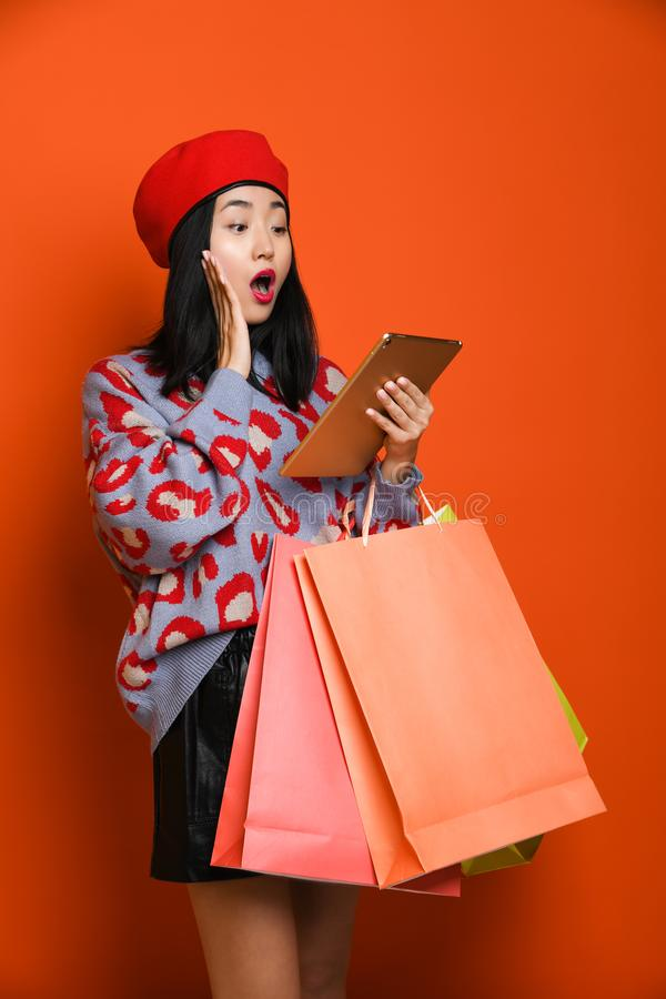 Woman holding shopping bag and using tablet for shopping online, shopping concept. Beautiful young happy Asian woman in a stylish beret and sweater, with a royalty free stock photography