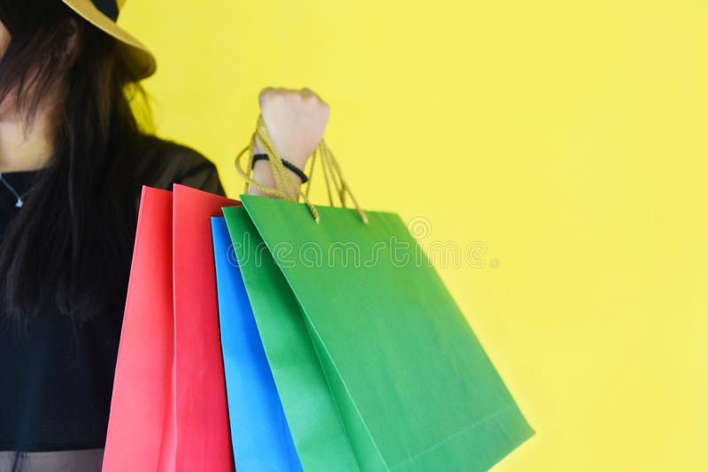 Woman holding shopping bags for girl fashion shopping in the summer colorful yellow stock photo