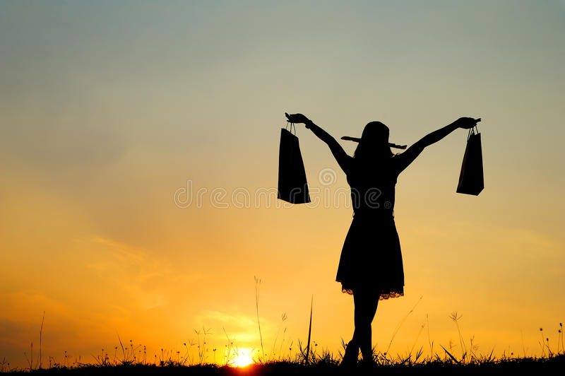 Download Woman Holding Shopping Bags In Sunset Silhouette Stock Photo - Image: 25243742