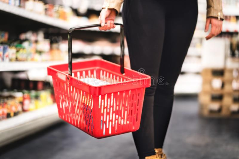 Woman holding shopping basket and walking in grocery store aisle stock photos