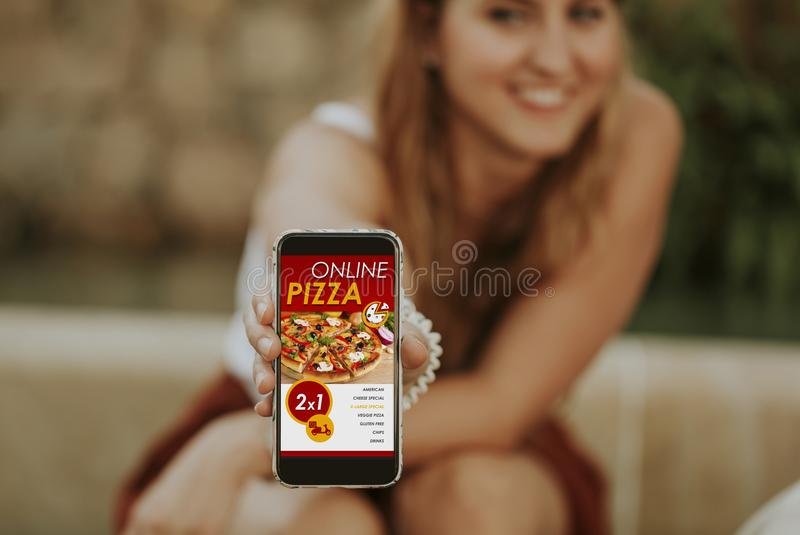 Woman holding and showing a mobile phone with online pizza delivery shop royalty free stock photos