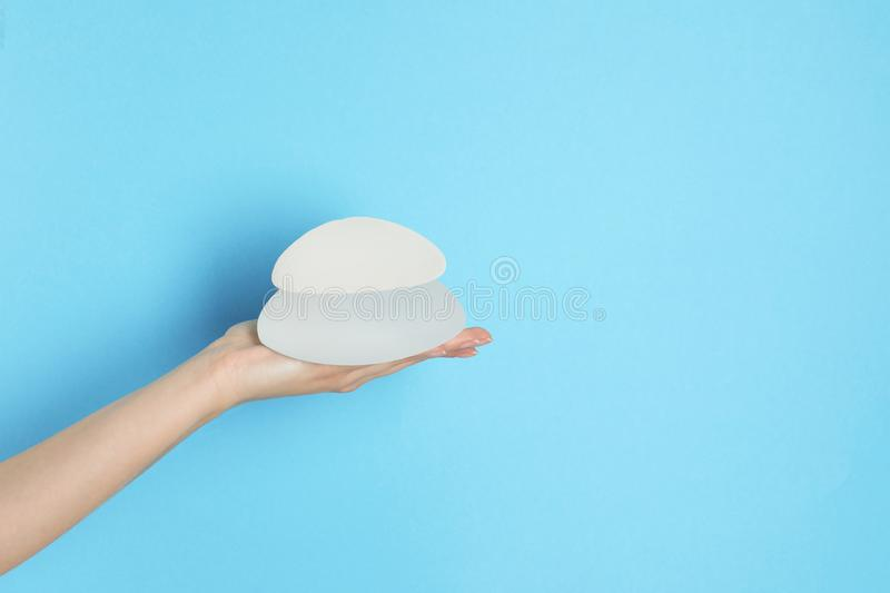 Woman holding silicone implants for breast augmentation on color background, space for text. Cosmetic surgery stock images