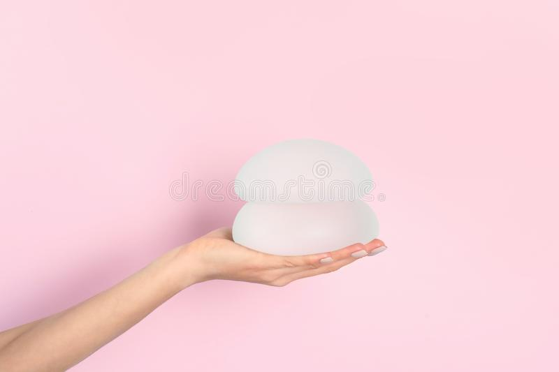 Woman holding silicone implants for breast augmentation on color background, space for text. Cosmetic surgery royalty free stock photos