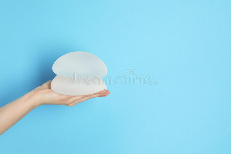 Woman holding silicone implants for breast augmentation on color background, space for text. Cosmetic surgery royalty free stock image