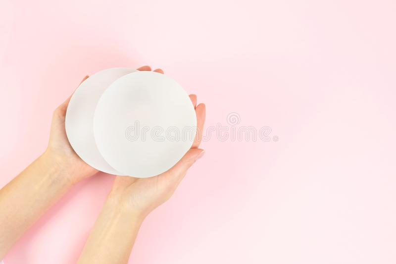 Woman holding silicone implants for breast augmentation on color background, top view with space for text. Cosmetic surgery stock photos