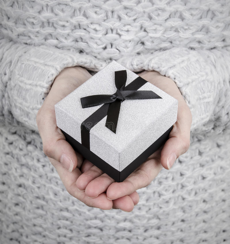 Woman holding silver gift box stock photos