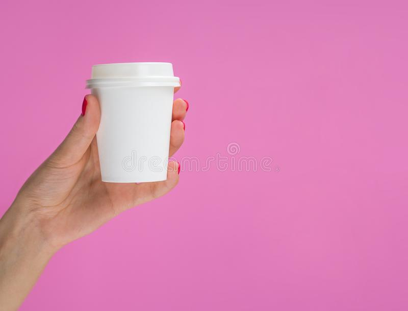 Woman holding small paper coffee cup isolated on pink. Female hand with red manicure holding white espresso cup. Mockup. With copy space on a cup stock photos