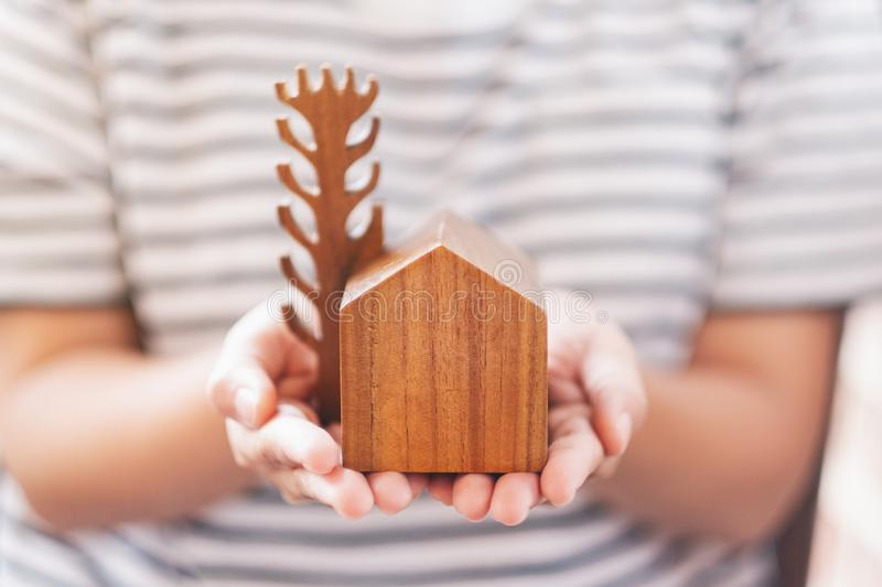 A woman holding a wooden house and tree model. A woman holding a small wooden house and tree model royalty free stock image