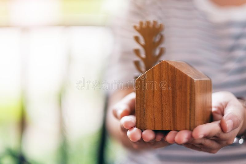 A woman holding a wooden house and tree model. A woman holding a small wooden house and tree model stock image