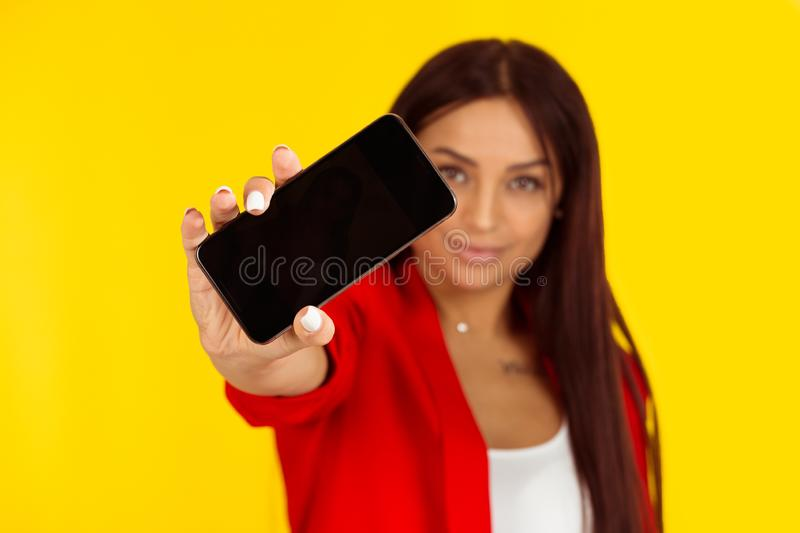 Woman holding smart phone with a blank black screen stock photos