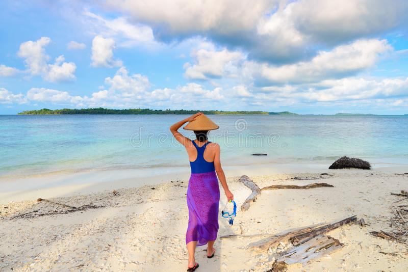 Woman holding snorkeling mask in hand walking on tropical beach. Rear view, traditional south asian hat turquoise sea dramatic sky stock images