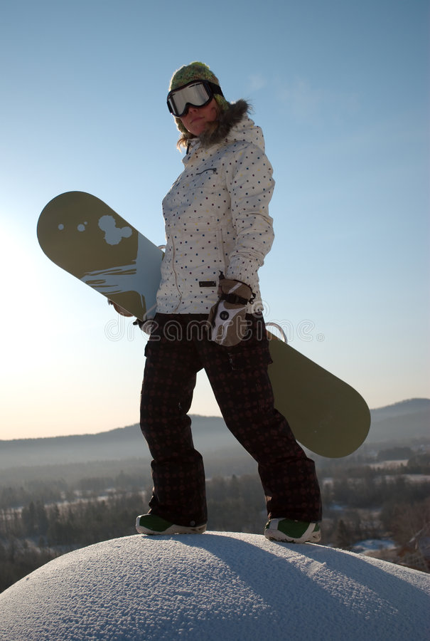 Woman holding snowboard. Close up of woman on top of hill wearing sky goggles and holding snowboard, winter sports scene stock images