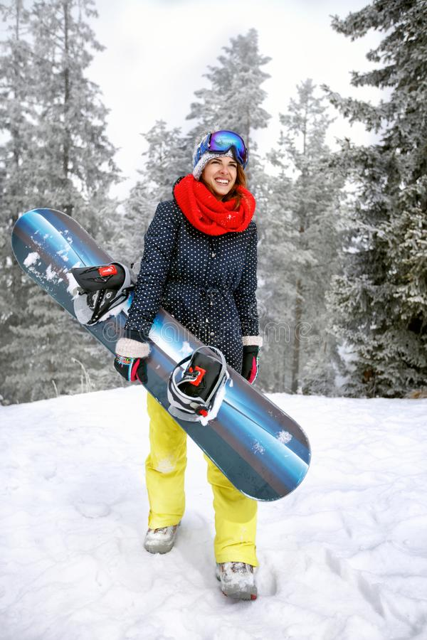 Woman holding snowboard in mountain. Woman holding snowboard in snowy mountain royalty free stock photos