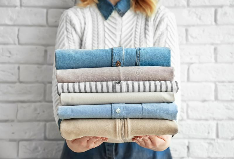 Woman holding stack of clean clothes near wall. Woman holding stack of clean clothes near brick wall royalty free stock images