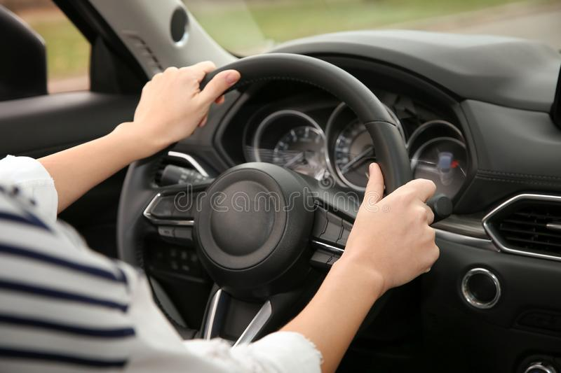 Woman holding steering wheel in car, closeup. royalty free stock image