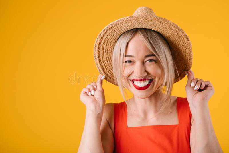 Woman holding straw hat. Amazing teth smile. Bright warm yellow background royalty free stock images