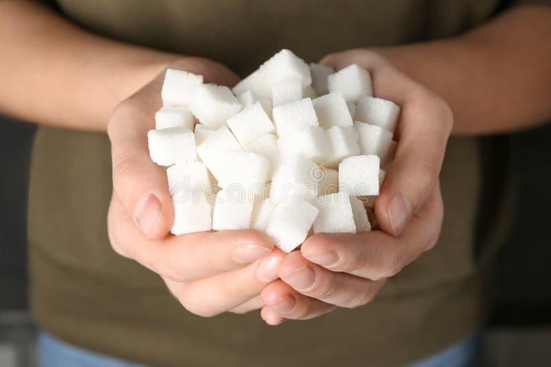 Woman holding sugar cubes, closeup stock images