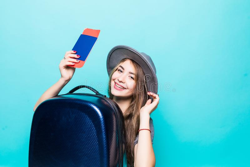 Young woman holding suitcase and passport looking up isolated on blue background. Woman holding suitcase and passport looking up. Isolated studio portrait stock image