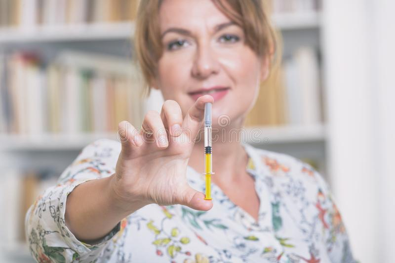 Woman is holding syringe with insulin or heparin stock photography
