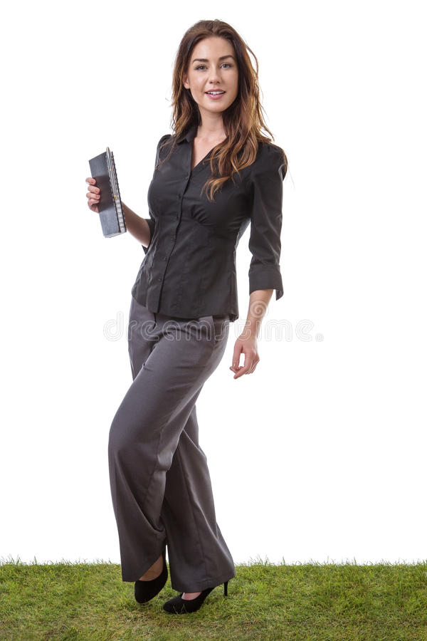 Woman holding tablet computer. Full length shot of a woman standing on on grass, holding a tablet computer, isolated on white stock images
