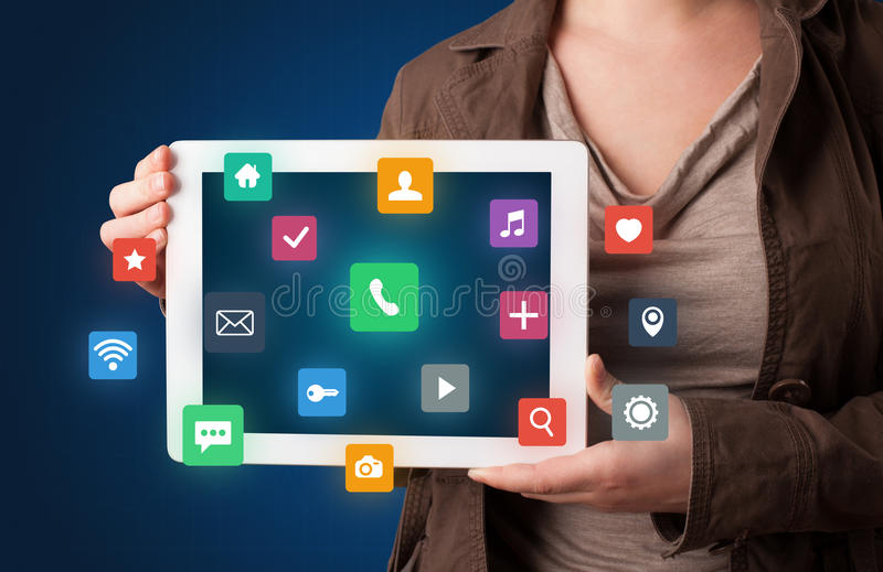 Woman holding tablet with multimedia graphics. Casual young woman holding tablet with colorful applications stock photos