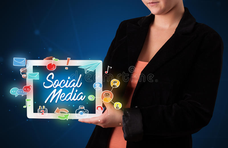 Woman holding tablet with social media graphics stock image
