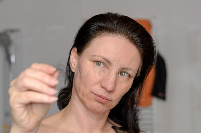 Woman holding a tangle of hair in her fingers. Which she has removed from the hairbrush after brushing her long brown hair stock photos