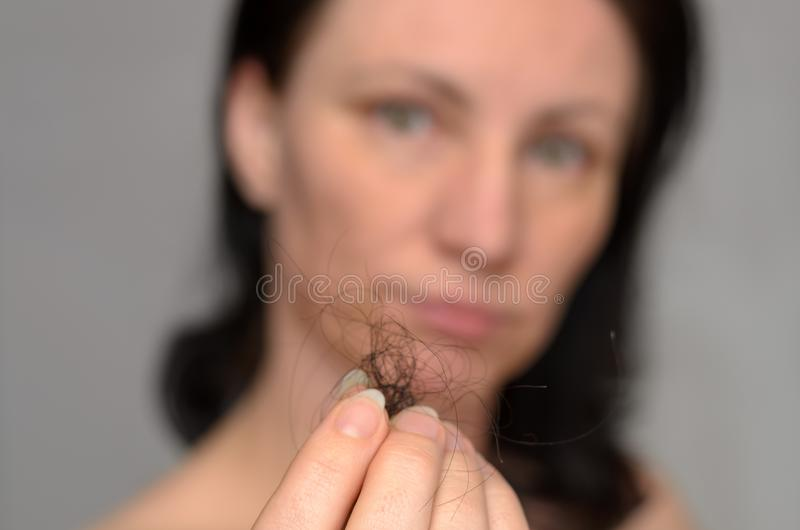 Woman holding a tangle of loose brown hair. In her fingers after removing it from the hairbrush with focus to her hand royalty free stock image