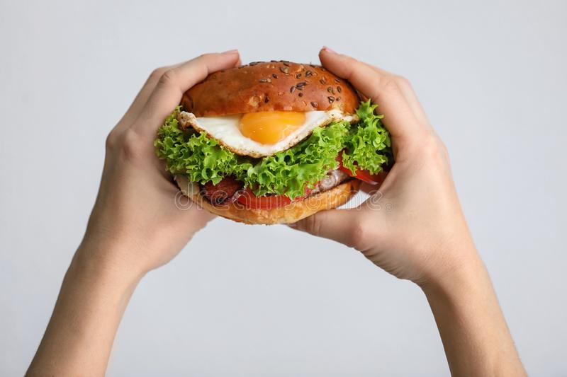 Woman holding tasty burger with fried egg. On light background stock images