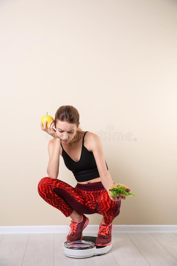 Woman holding tasty sandwich and apple while measuring her weight on floor scales near light wall. Weight loss motivation royalty free stock images
