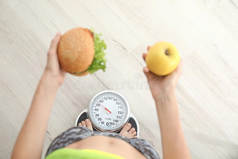 Woman holding tasty sandwich and fresh apple while measuring her weight on floor scales, top view. Choice between diet and unhealthy food royalty free stock image